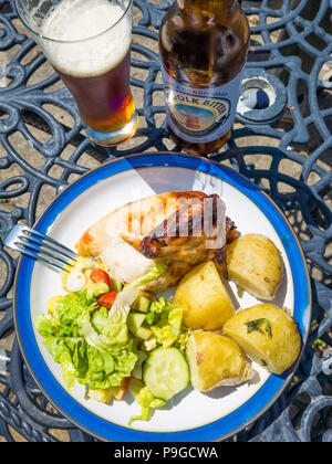 Lunch  a quarter roastt chicken eaten outdoors with new potatoes salad and a bottle of Norfolk Bitter beer - Stock Image