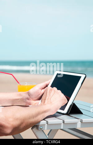 closeup of a young caucasian man on the beach, using a digital tablet, sitting at an outdoors table, next to a glass with a refreshing orange drink, a - Stock Image