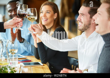 Friends toasting with glass of wine in restaurant at birthday party - Stock Image