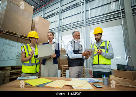 Warehouse managers and workers discussing with laptop and digital tablet - Stock Image