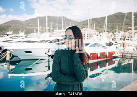 A beautiful stylish girl is standing against the backdrop of beautiful yachts in Porto Montenegro in Tivat in Montenegro. - Stock Image