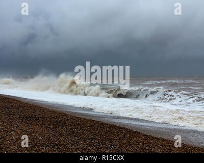Rough sea breaking on a shingle beach with froth and spray - Stock Image