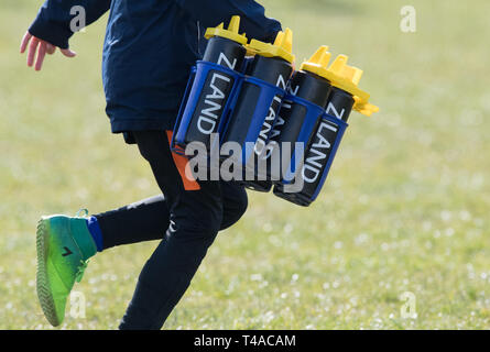Rugby support team member carrying water bottles - Stock Image