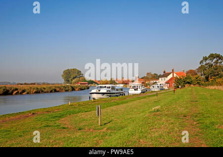 A view of boats moored on the River Bure on the Norfolk Broads at Stokesby, Norfolk, England, United Kingdom, Europe. - Stock Image