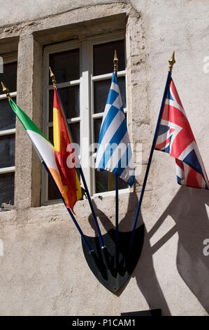 Flags including the Union Jack decorating the wall of a Pub on Rue Notre Dame Beaume France - Stock Image