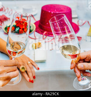 Clinking glasses of champagne in hands with party background - New Years' theme - Stock Image