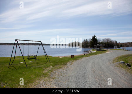 A little dirt road leads past a small beach with picnic table and swing set - Stock Image
