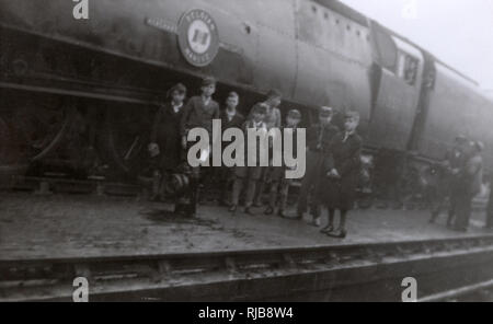 A group of school boys from Reigate Grammar School on a school trip to Nine Elms locomotive depot c.1948 standing on a platform next to a large steam engine. - Stock Image