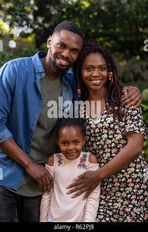 A mother, father and daughter holding each other affectionately in a garden - Stock Image