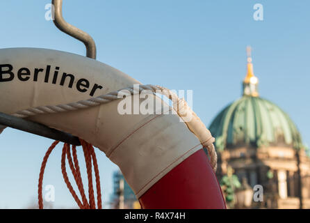 A life ring with 'Berliner' written on it across the Spree from the Berlin Cathedral. The dome is visible in the background. - Stock Image