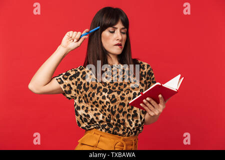 Image of a beautiful thinking young woman dressed in animal printed shirt posing isolated over red background writing notes in notebook. - Stock Image