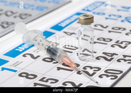 Transparent vial ampoule of a vaccine and syringe on a sheet of calendar - Stock Image