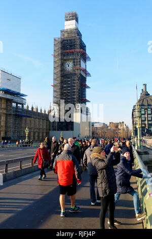 Tourists on Westminster Bridge and Big Ben clock tower covered in scaffolding , London, United Kingdom. - Stock Image