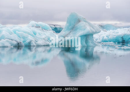 Blue icebergs floating on calm water with reflections in Jokulsarlon glacier lagoon. Iceland. - Stock Image