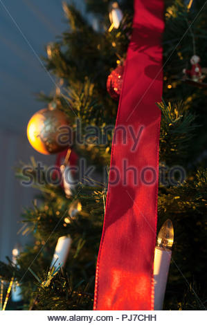 Christmas tree with golden ornament and red silk ribbon. - Stock Image