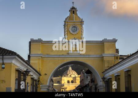 Spanish Colonial Architecture in Old City Antigua Guatemala with Santa Catalina Arch and Catholic Church Iglesia de la Merced in the Background - Stock Image