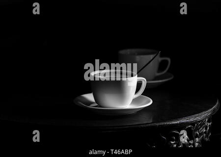 White cup of black coffee on black background - black and white rendering - coffee for two, copy space is plenty - Stock Image