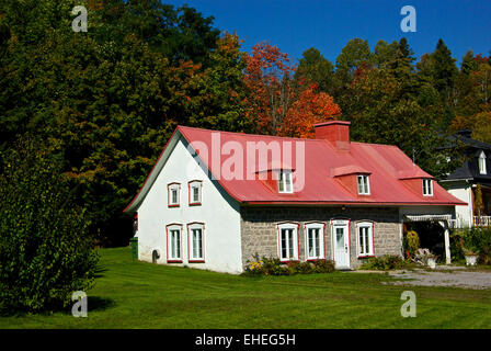 Old Quebec red ski jump roof plaster over stone farm house Chateau Richer QC - Stock Image