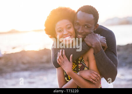 happy beautiful black race african couple in love or friendship stay together walking hugged with big smilies under the sunlight of the summer in vaca - Stock Image