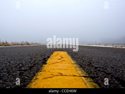 A low to the ground shot up a road on a foggy winter day. - Stock Image