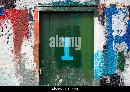 Number 1 door and paint covered wall in ship painters yard - Stock Image