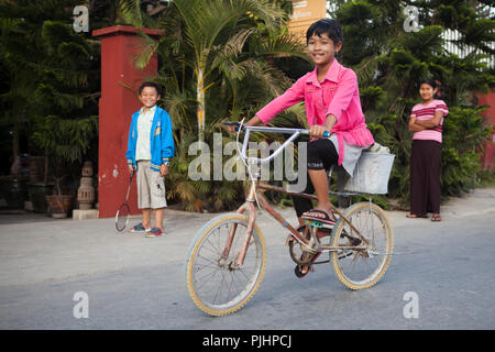 Child moving by bike in a street of Nyaungshwe, Burma - Stock Image