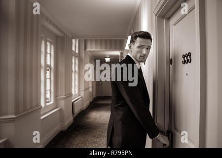 Good looking man in hotel corridor using key card to open room door - Stock Image