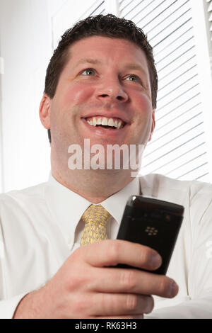 Upbeat Businessman Reacts to News on His Phone, USA - Stock Image