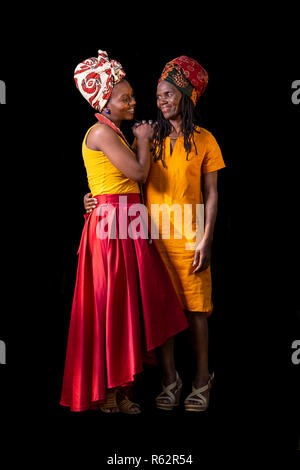 An African mother and daughter standing close together against a black background - Stock Image