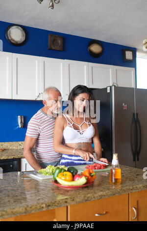 Older man and young woman enjoying cutting vegetables in their kitchen - Stock Image
