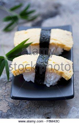 Tamago sushi (nigiri sushi with Japanese omlette) - Stock Image