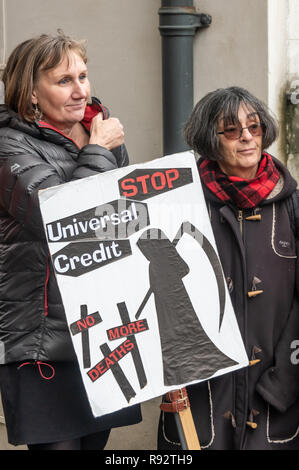 London, UK. 19th Dec, 2018. Maggie Zolobuaijluk (right) holds her placard with the grim reaper and message 'Stop Universal Credit - No More Deaths' at the protest by DPAC in support of the parliamentary debate due later in the day on the cumulative impact of the cuts on the lives of disabled people. They say the government cuts and changes in benefits, along with inappropriate benefit sanctions, have had a disproportionate effect on disabled people, resulting in great hardship, denying people their rights and many deaths. Credit: Peter Marshall/Alamy Live News - Stock Image
