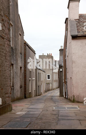Alfred Street in Stromness, Orkney with old paving stones from a quarry in Orphir and cobble stones in the centre of the street - Stock Image