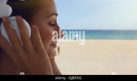 Closeup Portrait Handsome Young Woman Listening Music Player Headphones Sea Beach Background.Pretty Girl Enjoy Audio - Stock Image