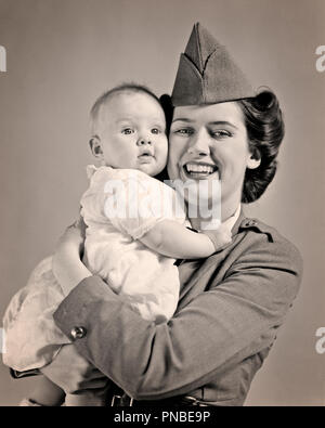 1940s SMILING WOMAN MOTHER WEARING ARMY UNIFORM LOOKING AT CAMERA HOLDING BABY  - a2705 HAR001 HARS OLD FASHION 1 JUVENILE INFANT EMBRACE STRONG PLEASED JOY CONFLICT FEMALES WW2 STUDIO SHOT HEALTHINESS HOME LIFE COPY SPACE HALF-LENGTH HUG LADIES DAUGHTERS PERSONS CARING EMBRACING B&W EYE CONTACT HAPPINESS TIGHT WORLD WARS WORLD WAR WORLD WAR TWO WORLD WAR II SMILES UNIFORMS JOYFUL WORLD WAR 2 PERSONAL ATTACHMENT AFFECTION EMOTION JUVENILES MID-ADULT MID-ADULT WOMAN MOMS TOGETHERNESS YOUNG ADULT WOMAN BABY GIRL BLACK AND WHITE CAUCASIAN ETHNICITY HAR001 OLD FASHIONED - Stock Image