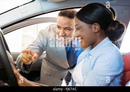 car sales consultant showing a new car to customer - Stock Image