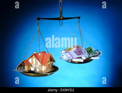 Model house and euro notes on a scale - Stock Image