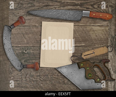 vintage kitchen knives and utensils over wooden board board, blank card for your text - Stock Image