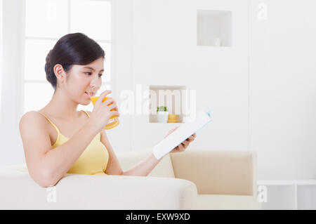Young woman drinking juice and reading a book, - Stock Image