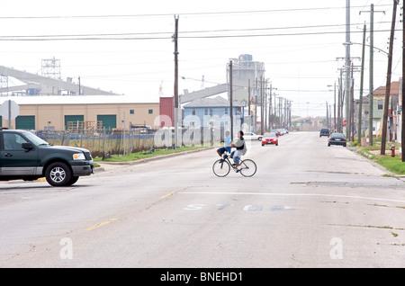Children on bicycle crossing road near poor neighborhood in Galveston, Texas, USA - Stock Image