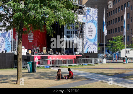 Montreal, Canada. 7/4/2018. A couple of women sitting in the shade before one of the free outdoor shows at the Montreal International Jazz Festival. - Stock Image