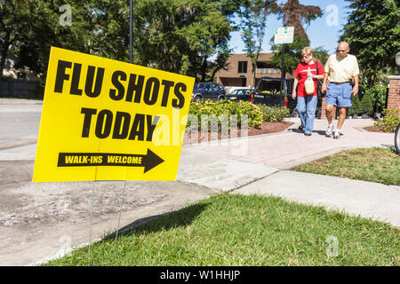 Winter Park Florida Farmers Market sign flu shots vaccine virus infection health pandemic prevention man woman couple senior wal - Stock Image