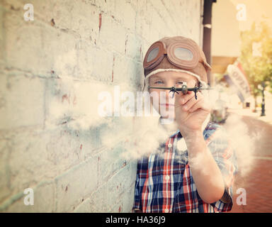 A young boy is pretending to be a pilot and playing with an airplane toy against a brick wall for a dream or career - Stock Image