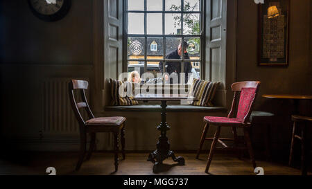 Open shuttered window lets the Cotswold's light spill onto the inviting antique table and chairs situated in The Bell Inn Moreton in Marsh - Stock Image