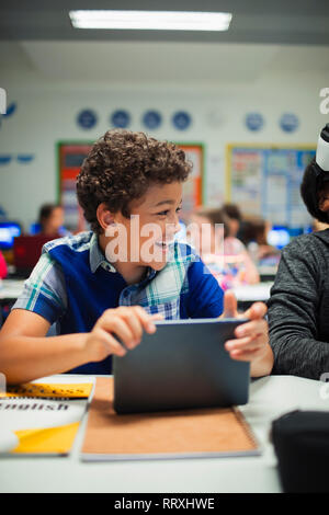 Happy elementary school boy using digital tablet in classroom - Stock Image