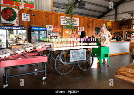 People shopping at rural country store with display of old fashion apple cider, peach cider and muscadine cider in Pike Road Alabama, USA. - Stock Image