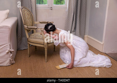 Depressend youg woman in authentic regency dress holding a letter and leaning against an antique chair - Stock Image