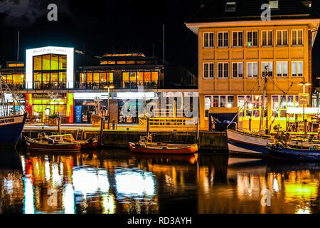 Illuminated shops and cafes in the evening as boats dock along the Alter Strom canal in the Baltic city of Warnemunde, Germany. - Stock Image