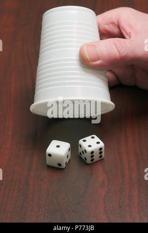 two dice and a plastic cup - Stock Image