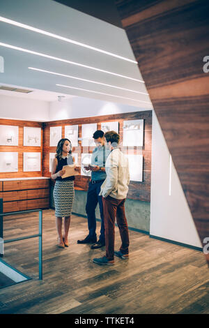 Happy business people discussing while standing in office - Stock Image